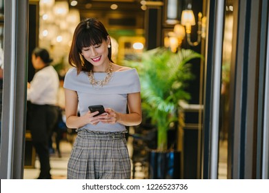 A Chinese Asian woman (Singaporean) woman is smiling happily as she checks her smartphone during the day in the doorway of her office. She is elegantly dressed and beautiful.