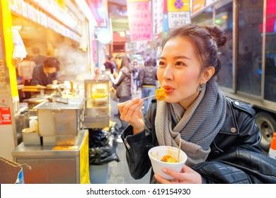 Chinesisches junges asiatisches Frauenmodell mit chinesischer gedünsteter Dumpling auf der Straße in Hongkong