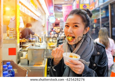 Chinese Asian young female model eating Chinese Steamed Dumpling on Street in Hong Kong