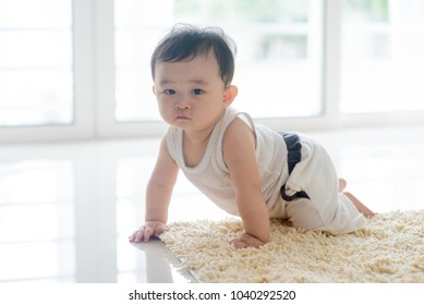 Chinese baby boy crawling on carpet. Asian family at home, living lifestyle indoors.