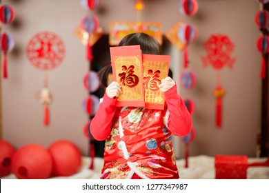 Chinese baby girl  traditional dressing up with a FU means lucky red envelope against  FU means lucky ornament background