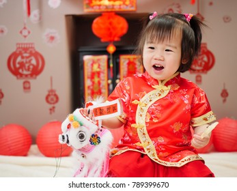 "Chinese baby girl  traditional dressing up celebrate Chinese new year.the small chinese dancing lion with ""zhao cai jin bao"" means ""more wealth will coming in"""
