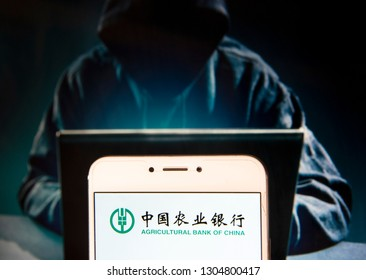 Chinese banking company Agricultural Bank of China logo is seen on an Android mobile device with a figure of hacker in the background.