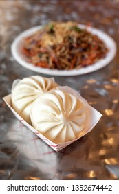 Chinese baozi dumplings with a chow mien noodle dish in the background, in a restaurant menu item combination
