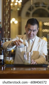 Chinese barman is making Fruit cocktail with dry ice