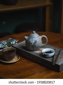 Chinese black tea set on the wooden table. ceramic tea pod flower painted. tea leaf, tea board, blurred background