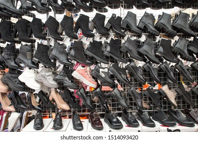 Chinese black women's boots and sneakers hang in rows in the market. Sale is not qualitative women's shoes. Russia, Abakan 23.09.2019