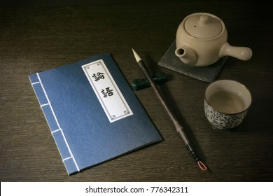 Chinese book title Confucius Analects on top of wooden table, brush pen and Chinese tea pot , tea cup