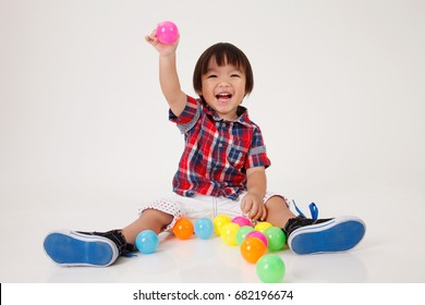 chinese boy sitting down playing with toys