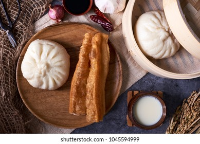 Chinese breakfast: Steamed buns (Baozi), fried breadsticks (youtiao) and soy milk. Flat lay, overhead top view