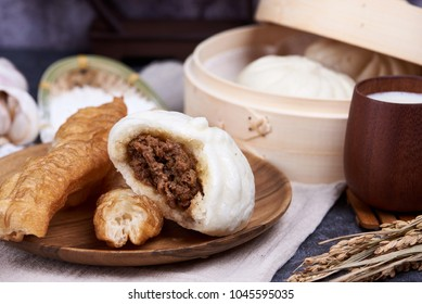 Chinese breakfast: Steamed buns (Baozi) and fried breadsticks (youtiao) on wooden plate, with bamboo steamer in background. soy milk.