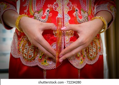 Chinese bride in traditional chinese wedding dress with heart shaped gesture