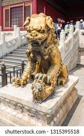 Chinese bronze qilin statue next to the white stone stairs.