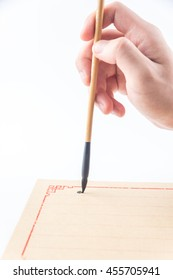 Chinese brush in hand and writing on the Chinese stationery