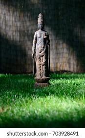 Chinese Buddhist Bodhisattva iron statue resting in green grass with straw background