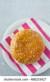 Chinese bun with green bean paste and sesame seeds on a colorful napkin with stripes.