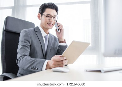 Chinese business man talking on a mobile phone and working on his laptop