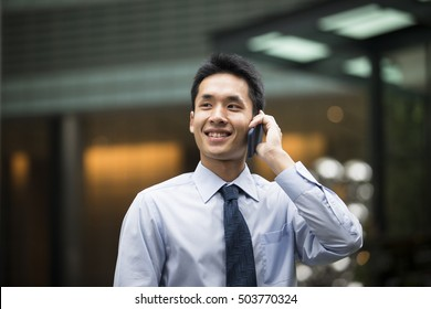 Chinese business man talking on a mobile phone.