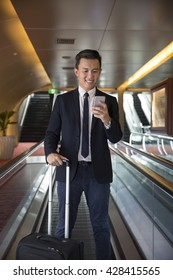Chinese business Man using his Smart phone on a moving walkway/travelator.