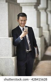 Chinese business Man using his Smart phone outdoors in Asian city.