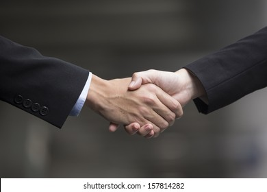 Chinese Businessman and businesswoman shaking hands outside the office
