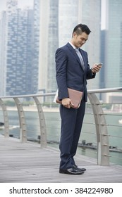 Chinese businessman standing outdoors and using his Smart phone in modern Asian city. Business on the go concept.
