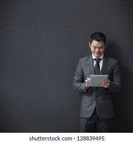 Chinese businessman using a tablet computer and leaning against a black wall.