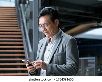 Chinese businessman wearing a jacket, smiling and looking at the cellphone in his hand.