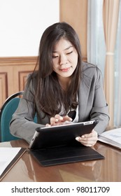Chinese businesswoman busy with her tablet in the office