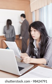 Chinese businesswoman looked shocked examining document in the office