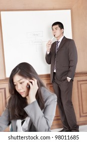 Chinese businesswoman on the phone while businessman preparing presentation on background
