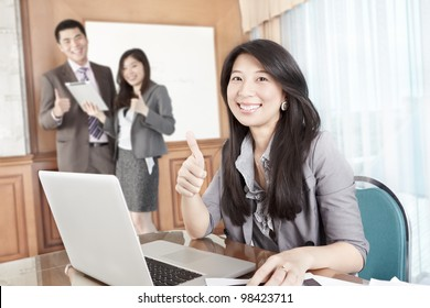 Chinese businesswoman showing her thumb up in the office