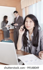 Chinese businesswoman talking on cell phone in the office