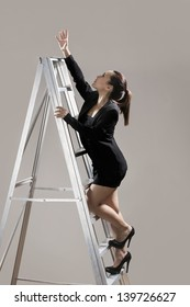 Chinese businesswoman wearing a dark suit and climbing a ladder. Conceptual image about ambition and success.