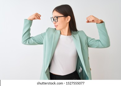 Chinese businesswoman wearing elegant jacket and glasses over isolated white background showing arms muscles smiling proud. Fitness concept.