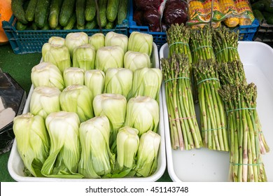 Chinese cabbage bok choy and bundles of fresh asparagus displayed in market stand on Naschmarkt in Vienna, Austria
