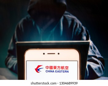 Chinese carrier China Eastern Airlines logo is seen on an Android mobile device with a figure of hacker in the background.