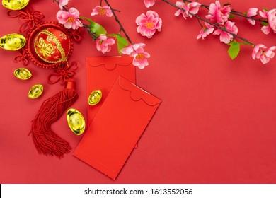 Chinesischer Charakter bedeutet Glück und Glück.Accessoires auf Mond Neujahr & Chinesisches Neujahrskonzept Hintergrund.Rote Blume und rosafarbene Blume mit Orange auf modernen roten Tapeten.Kopienraum.