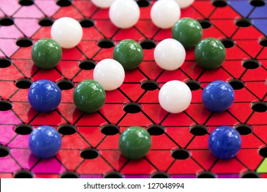 A Chinese checkers board and different color marbles