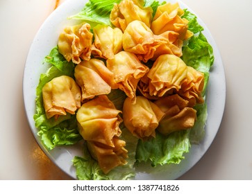 Chinese cheese wontons appetizer served on bed of lettuce leaves