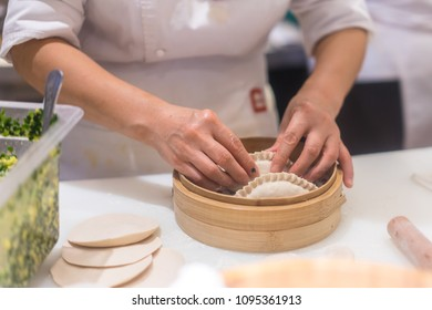 Chinese chef making dumplings in kitchen