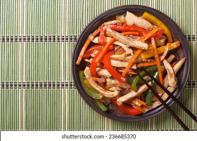 Chinese chicken with vegetables close-up on a plate. horizontal view from above
