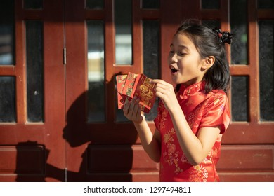 Chinese children in traditional costume holding red packet of money and smiling.