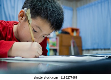 chinese children writing paper with pencil, boy doing homework, boy writing on paper
