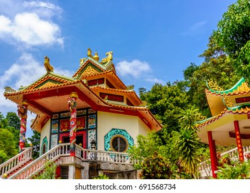 The Chinese church of the Buddhist temple on the hill top with a blur background of trees from behind, under blue sky