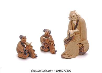 Chinese clay sculpture of Confucius reading a book with students, isolated on white background  with copy space