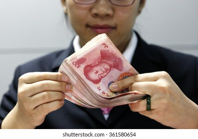 A Chinese clerk counts RMB (renminbi) yuan banknotes at a bank in Huaibei ,  Anhui province, China 1 December 2015.