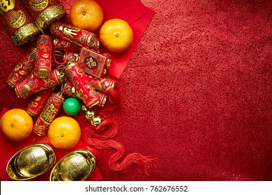 Chinese coins luck and firecrackers or chinese knot and Chinese gold ingots and Traditional (Foreign text means lucky blessing) and red envelopes and decoration with fresh oranges on red paper