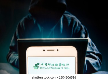 Chinese commercial retail bank Postal Savings Bank of China (PSBC) logo is seen on an Android mobile device with a figure of hacker in the background.