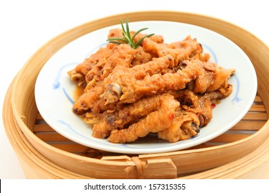 Chinese Cooked Chicken Feet in bamboo steamer on white